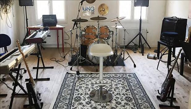 Book et øvelokale MusikLaboratoriet fls. Billede af øvelokale med keyboards, bas, guitar, trommesæt, højtalere og en stol, der står på et tæppe i midten af lokalet.