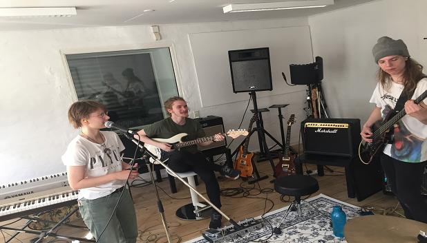 Band. Billedet viser tre unge i et øvelokale, én står op og spiller bas, én står og synger og én sidder og spiller guitar.