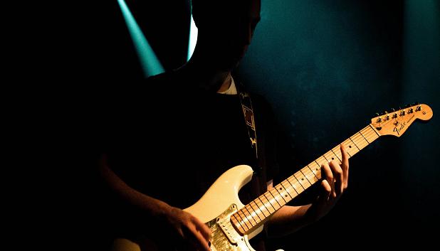 Guitar. Billedet viser en person, der står i skygge, og spiller på en guitar, hvor der er spot på.