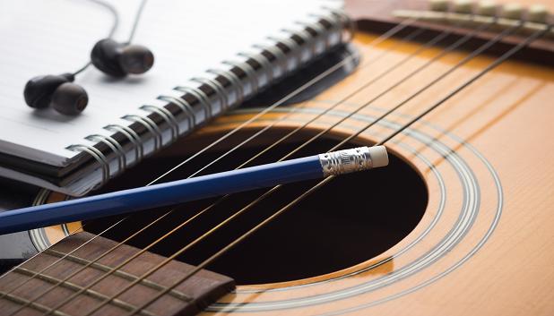 Sangskrivning fls. Billedet viser et udsnit af en guitar, hvorpå der ligger en blok, en blyant og et in-ear headset.