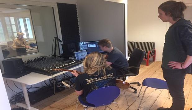 Musiklaboratoriet 1. Tre unge i et øvelokale med mixerpult og et par skærme.
