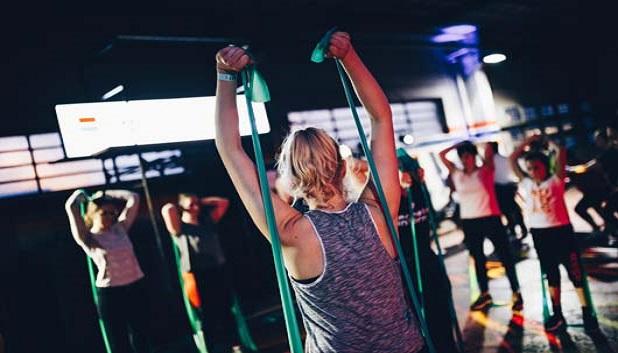 fitness fo alle. Instruktør viser øvelser med elastik for en gruppe unge