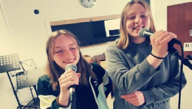 Musk S├©hus9. To piger står og synger i mikrofoner