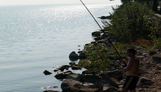 Go Fishing fls. En person står og fisker med stand ved havet